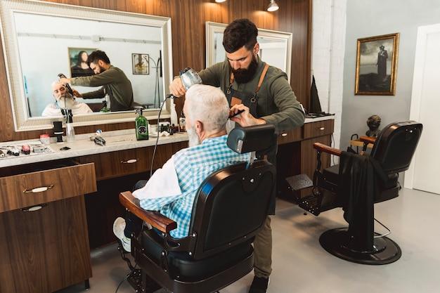 Friseur, der bart zu gealtertem kunden im salon anredet Kostenlose Fotos