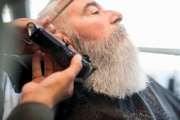Friseur, der bart zum gealterten mann trimmt Kostenlose Fotos