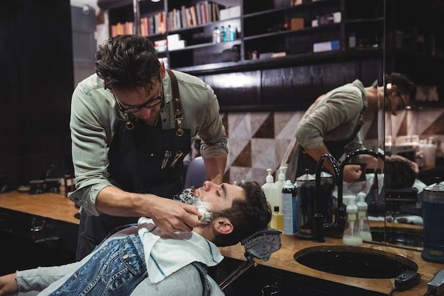 Friseur, der creme auf kundenbart aufträgt Kostenlose Fotos