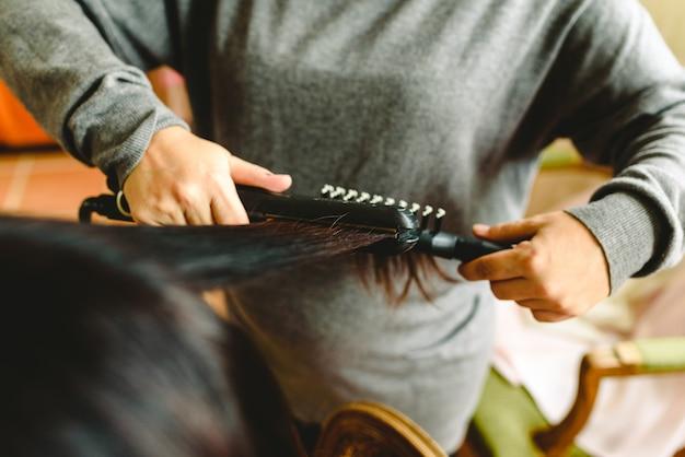 Friseur, der das dunkle haar eines kunden glatt macht. Premium Fotos