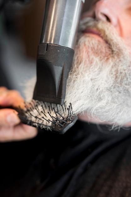 Friseur, der dem kunden bart im salon anreden lässt Kostenlose Fotos