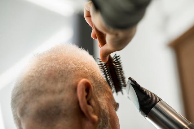 Friseur, der dem mann im salon das anreden macht Kostenlose Fotos