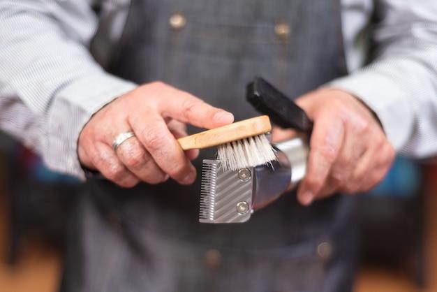 Friseur, der elektrischen haarschneider säubert. Premium Fotos