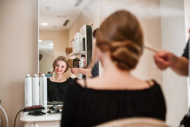 Friseur, der frauenhaar mit haarspray repariert Premium Fotos