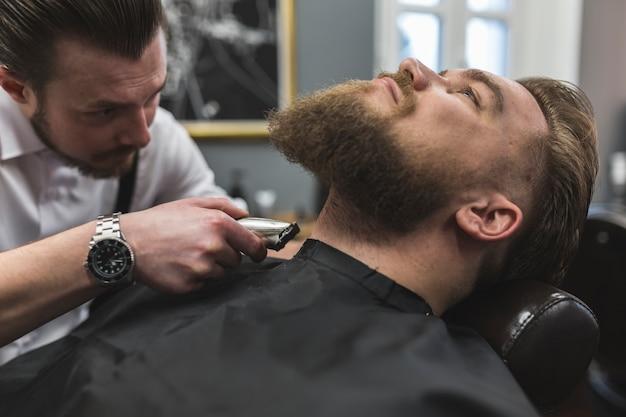 Friseur, der Hals des Kunden rasiert | Download der kostenlosen Fotos