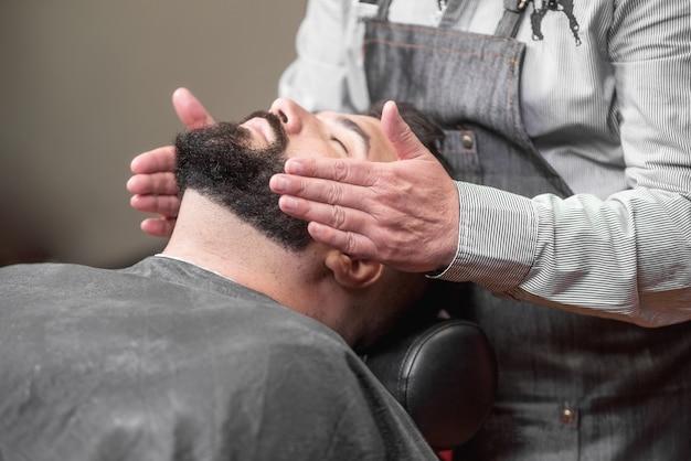 Friseur, der lotion am friseursalon nach dem rasieren zutrifft. Premium Fotos