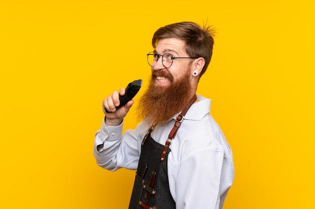 Friseur mit langem bart in einem schutzblech über lokalisierter gelber wand Premium Fotos