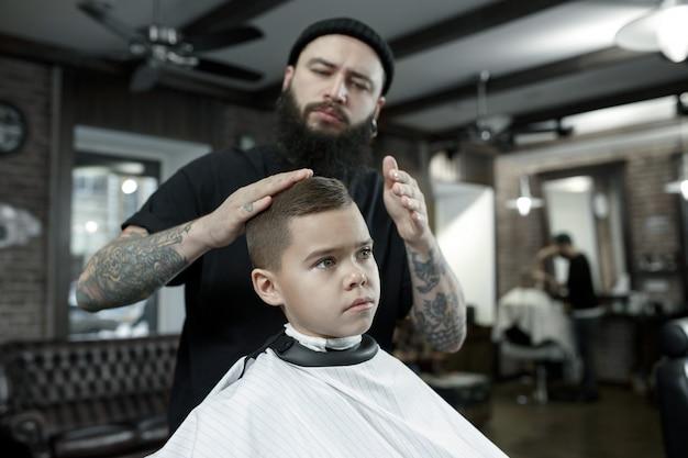 Friseur schneidet die haare des kleinen jungen Kostenlose Fotos