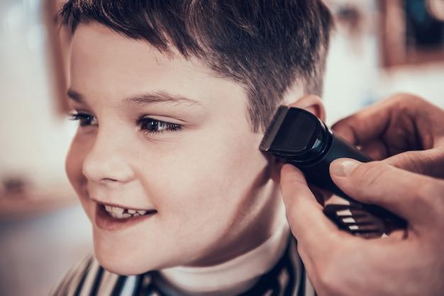 Friseur schneidet hübsche kinderseiten mit rasiermesser aus Premium Fotos