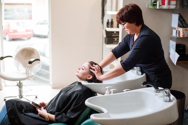 Friseur und frau während der haarwäsche Premium Fotos