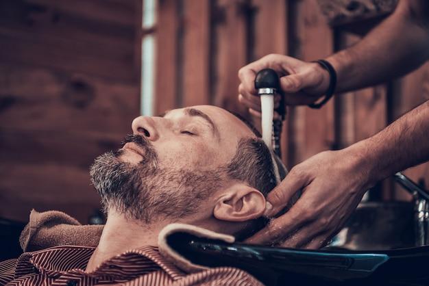 Friseur wäscht kunden-schwarzes haar vom hahn Premium Fotos