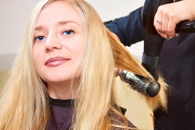Friseurhände, die langes blondes haar trocknen Premium Fotos