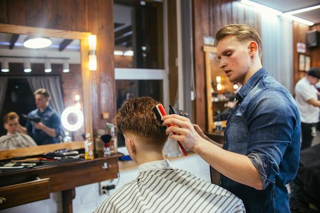 Friseurjungenhaarschnitt-friseur im friseurladen. Premium Fotos