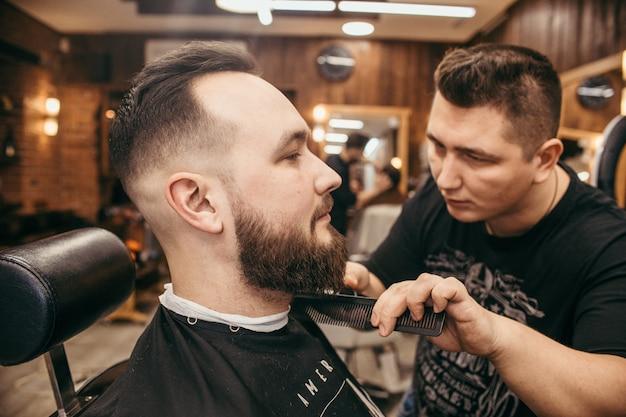 Friseursalon, ein mann mit bartschnitt friseur Premium Fotos