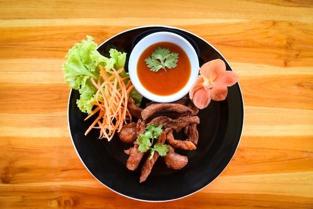Frittiertes rindfleisch oder schweinefleisch mit soße und frischgemüse auf platte in der draufsicht des holztischs. thailändisches gebratenes sonnengetrocknetes rindfleisch-asiatslebensmittel Premium Fotos