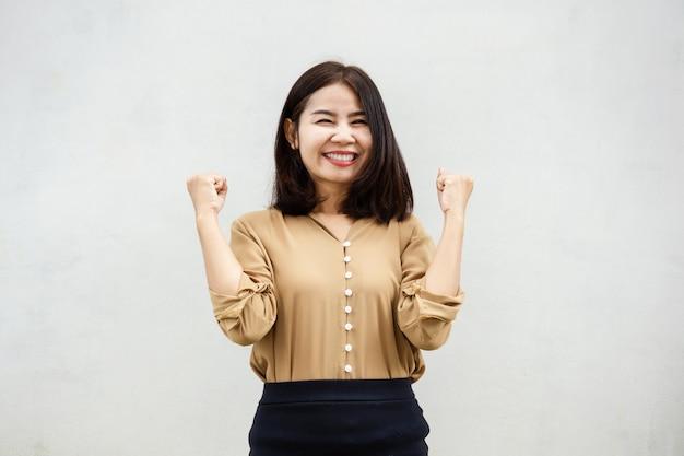 Fröhliche asiatische geschäftsfrau lächelnd gegen graue wand Premium Fotos