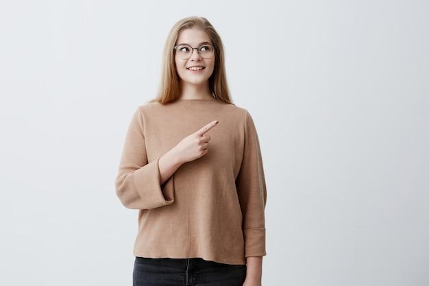 Fröhliche blonde europäische weibliche punkte mit dem vorderfinger beiseite auf dem kopierraum, hat weiße perfekte zähne und ein breites lächeln. charmantes mädchen lässig gekleidet bewirbt etwas an der leeren wand Kostenlose Fotos