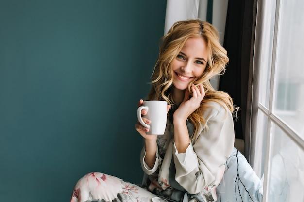 Fröhliche blonde frau, die sich entspannt und auf der fensterbank sitzt und eine tasse kaffee, tee hält. sie hat langes blondes, welliges haar und ein schönes lächeln. trage einen schönen pyjama in blumen. Kostenlose Fotos