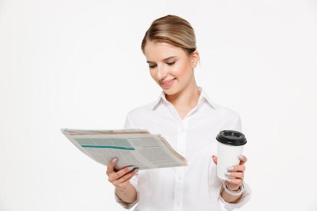 Fröhliche blonde geschäftsfrau, die zeitung liest, während tasse kaffee über weißer wand hält Kostenlose Fotos