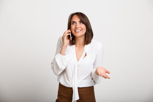 Fröhliche bürodame, die am telefon spricht Kostenlose Fotos