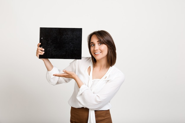 Fröhliche bürodame, die banner auf schwarzer zwischenablage zeigt Kostenlose Fotos