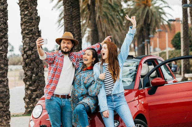 Fröhliche, die selfie nahe rotem auto in der straße nehmen Kostenlose Fotos