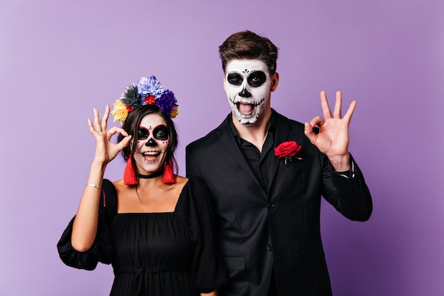 Fröhliche dunkelhaarige jungen und mädchen lächeln und zeigen zeichen ok. porträt der fröhlichen mexikanischen dame und des mannes mit gemalten gesichtern. Kostenlose Fotos