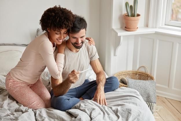 Fröhliche dunkelhäutige frau umarmt ihren ehemann, zeigt positives testergebnis, freut sich, dass sie bald eltern werden, Kostenlose Fotos