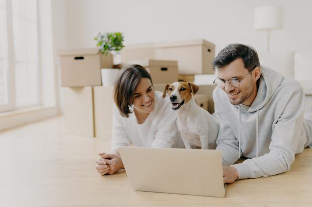 Fröhliche ehemänner und ehefrauen schauen sich filme online auf dem laptop an, ruhen sich auf dem boden aus, entspannen sich und unterhalten sich, ihr haustier posiert dazwischen, ziehen in ein neues zuhause um, posieren im geräumigen wohnzimmer mit ausgepackten kisten Premium Fotos