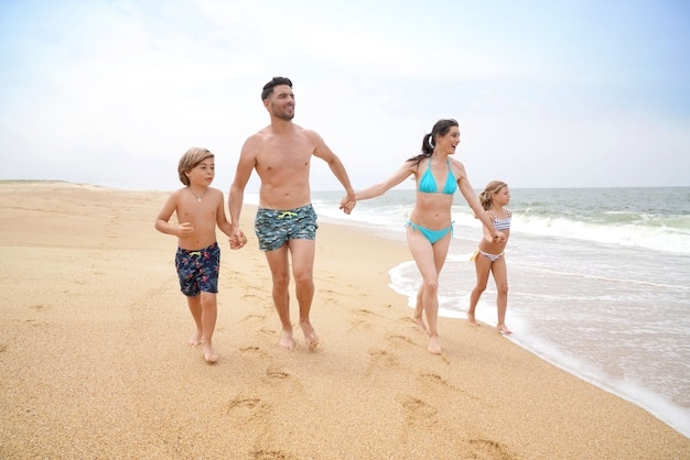 Fröhliche familie läuft am sandstrand Premium Fotos