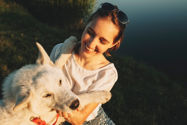 Fröhliche frau im weißen hemd und in der sonnenbrille, die großen weißen hund umarmt, der zusammen mit geschlossenen augen an der wasserquelle sitzt Premium Fotos
