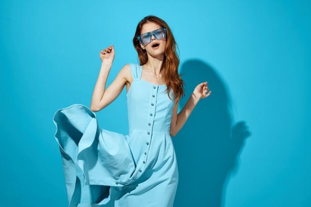 Fröhliche frau im weißen kleid, das isolierten hintergrund der blauen brille studio aufwirft. hochwertiges foto Premium Fotos
