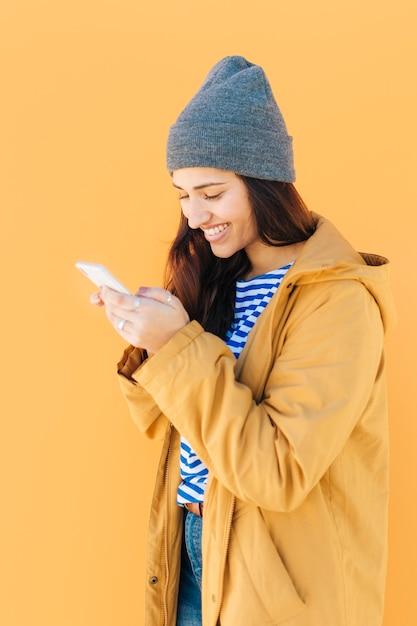 Fröhliche frau in gelber jacke mit handy Kostenlose Fotos