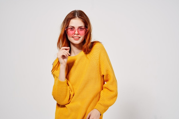 Fröhliche frau in rosa brille gestikuliert mit ihren händen gelben pullover studio. hochwertiges foto Premium Fotos
