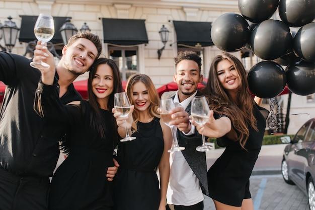 Fröhliche freunde, die champagner auf der party im freien trinken Kostenlose Fotos