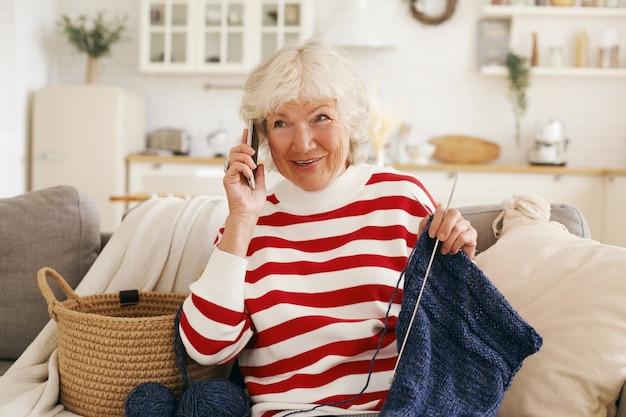 Fröhliche, freundlich aussehende, grauhaarige, ältere frau in freizeitkleidung, die auf einem sofa mit nadeln und einem garten sitzt, ein nettes telefongespräch mit ihrer alten freundin führt, klatscht und die neuesten nachrichten teilt Kostenlose Fotos