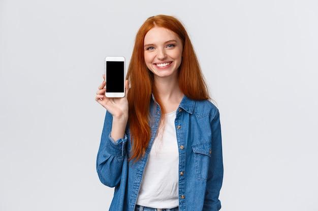 Fröhliche freundliche rothaarige frau, die wasser-app prüft, bleiben mit smartphone-anwendung hydratisiert Premium Fotos