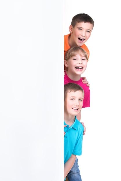Fröhliche gruppe von kindern hinter weißem banner - lokalisiert auf weißem hintergrund. Kostenlose Fotos