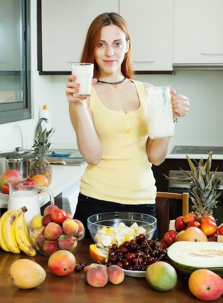 Fröhliche hausfrau trinkt milchcocktail mit früchten Kostenlose Fotos