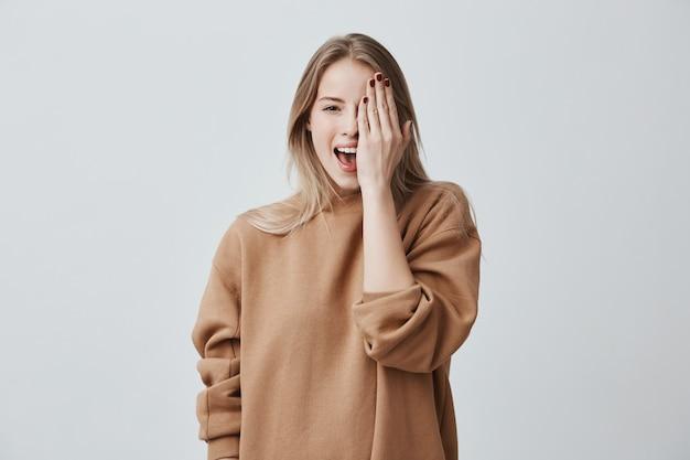 Fröhliche hübsche charmante frau im losen pullover mit hellem haar, das glücklich lächelt, spaß drinnen hat und ein auge mit der hand schließt. Kostenlose Fotos