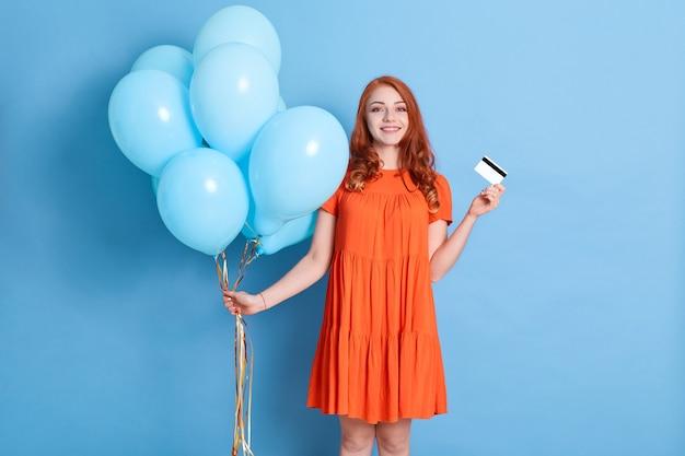 Fröhliche hübsche junge frau, die kreditbankkarte hält und mit heliumballons feiert, die über blaue wand lokalisiert werden Premium Fotos