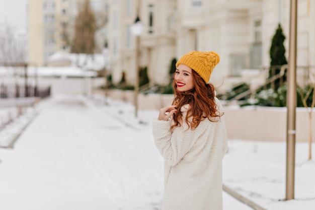 Fröhliche ingwerfrau, die zurück schaut, während sie um winterstadt geht. anmutiges europäisches mädchen, das im verschneiten morgen kühlt. Kostenlose Fotos