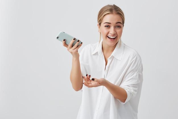 Fröhliche junge blonde studentin, die freudig mit den zähnen mit dem handy lächelt und newsfeed auf ihren konten des sozialen netzwerks überprüft. hübsches mädchen, das internet auf dem handy surft Kostenlose Fotos
