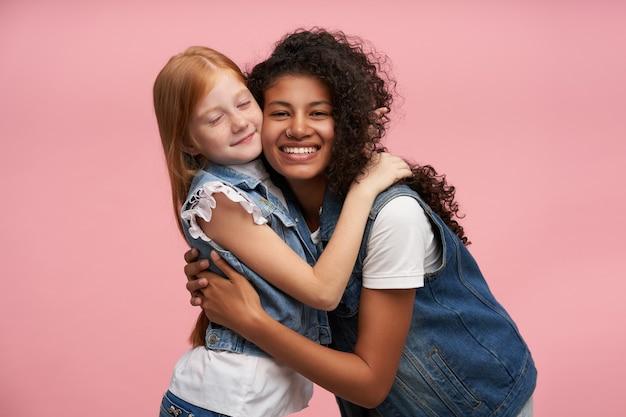 Fröhliche junge dunkelhäutige brünette frau mit langen lockigen haaren, die glücklich lächeln und niedliches positives rothaariges weibliches kind kuscheln, lokalisiert auf rosa Kostenlose Fotos