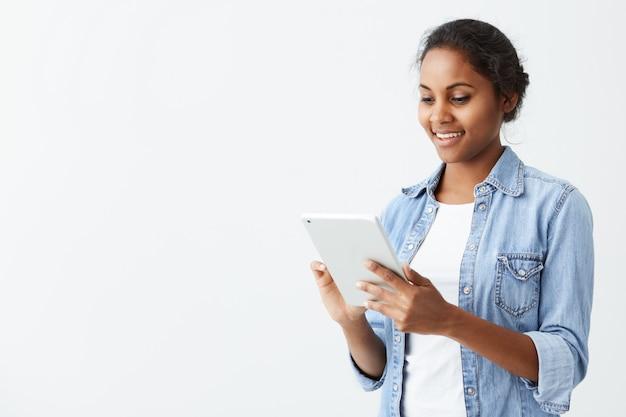 Fröhliche junge dunkelhäutige studentin mit niedlichem lächeln, das auf weißer wand steht, tablette benutzt, newsfeed auf ihren konten des sozialen netzwerks prüfend. hübsches afroamerikanisches mädchen, das internet auf t surft Kostenlose Fotos