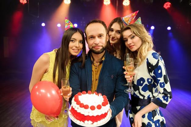 Fröhliche junge firma feiert geburtstag in einem nachtclub Premium Fotos