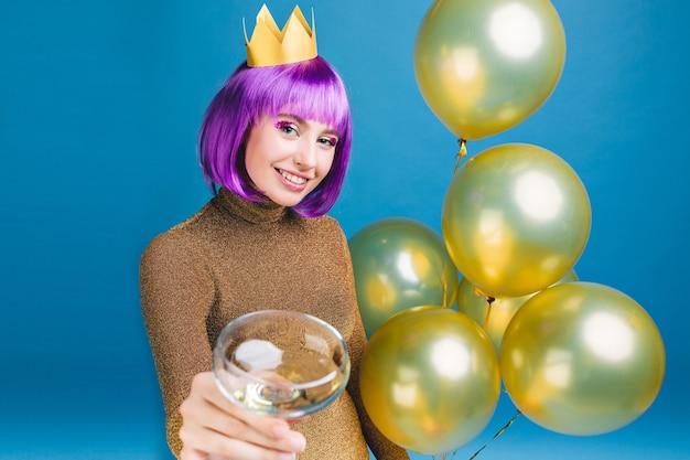 Fröhliche junge frau mit lila haarschnitt, die neujahrsparty mit goldenen luftballons und champagner feiert. luxuskleid, krone auf dem kopf, geburtstag, alkoholcocktail trinkend. Kostenlose Fotos