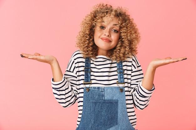Fröhliche junge frau mit lockigem haar, das freizeitkleidung trägt und schultern zuckt Premium Fotos