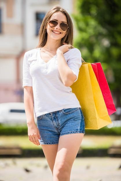 Fröhliche junge frau mit sonnenbrille mit zwei einkaufstüten Premium Fotos