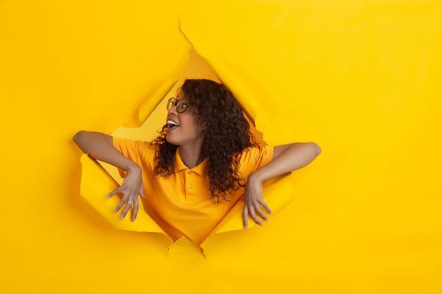 Fröhliche junge frau wirft in zerrissenem gelbem papierlochhintergrund, emotional und ausdrucksstark auf Kostenlose Fotos
